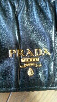 PRADAについて PRADAの財布をPRADAのe-store(公式サイト?)で買ったのですが、財布の「PRADA」のエンブレムのRの部分に切り込み?がないのですがこれが普通なのでしょうか? サイトでの写真では切り込みがあるよ...