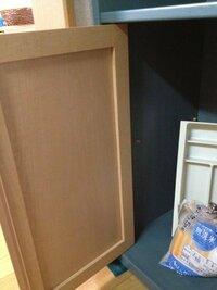 食器棚の扉の取り外し方がわかる方いませんか?(写真あり) 写真ように、蝶番タイプのものではなく 板の上下から留めてあるタイプのものです。 よーく見ると、扉と上の板の隙間に、黒くて丸いパーツ(ワッシャーのような形)があります。  試しに上に乗っている板をグッと持ち上げ、 扉を外そうと試みましたが 上下にガタガタと動くだけで外れません。  食器棚を持ち上げて、下から何かネジ等を外...