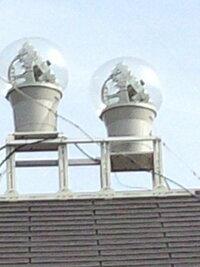 屋根の上の不思議なガラス玉 これは何?? 自宅(東京都町田市)の近くの一般住宅の屋根の上に、添付写真のような丸いガラスの球が載っています。大きさは結構大きく、おそらく直径50センチ以上あると思います。これが何かご存じの方がいたら教えてください。ちなみに、常々不思議に思っていたら、これと同じものを東京都狛江市(小田急線から見えます)や兵庫県川西市多田院付近でも見つけました。他にも結構あるのでは...