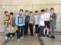 韓国の男性アイドルグループPENTAGONについてです。 下の写真の右から4番目の水色のシャツにピンクの靴を履いてる方はどなたでしょうか? 名前を教えてください。よろしくお願いします!