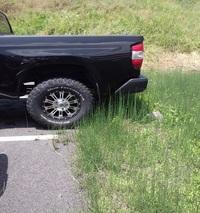 駐車場のはみ出しについて教えてください。  車がはみ出して駐車されています。草が生えている所が私有地です。 タイヤの位置は駐車場の中ですがこの場合注意してもいいですか? 車が大きいのでこのような停め...