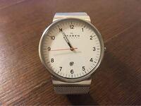 腕時計教えてください。 スカーゲンのこの写真と同じ白い文字盤に赤オレンジの秒針で、黒革のベルトの腕時計の型番を教えてください。 厳密でなくて良いので、画像だけでも良いです。 1万五千円〜二万円くらいの腕時計。
