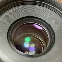 カメラレンズを中古で買いました。 このC 型の光はなんですか?  部屋の上にある電球の反射なのでしょうか