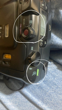 PENTAXのESPIO115のフィルムカメラを使っているのですが、この画像の白丸の所の花のマークはなんですか?? あと、電源ボタンのところにある□とPの□のマークは何が違いますか?あと、巻き戻しボタンがどこにあるのか知りたいです。