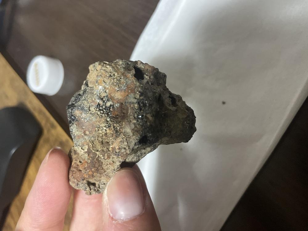 隕石や石に詳しい方にお聞きしたいのですが、こちらの石は隕石の可能性がありますか? 先日、息子が畑から拾ってきた石です。 赤茶色のゴツゴツした石の一部が黒曜石の様な質感になっており、黒いキラキラした部分も見られます。全体的に穴が空いており、磁石にくっつきます。