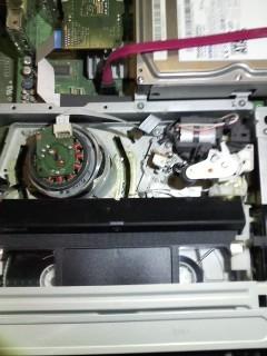 ビデオテープが取り出せません。 sharp製 DV-ACV52 (2008.12購入)です。 コンセントを抜き通電しましたがダメ。 youtubeの https://www.youtube.com/watch?v=G44nM006wmg&list=FLS_G9o7e1EB24SjmbGcH3MA&index=3 の動画にヒントがあると思いましたが、 蓋を開けても回せるところが見つからず、詰んでしまいました。 修理に出す前に自分でできることがありましたら、 どうか精通している方、コメントを頂けると助かります。 中のVHS部分を撮影した画像を添付いたします。 テープはダメになっても全然かまいません。 直せる方法がありましたら、よろしくご教示ください。