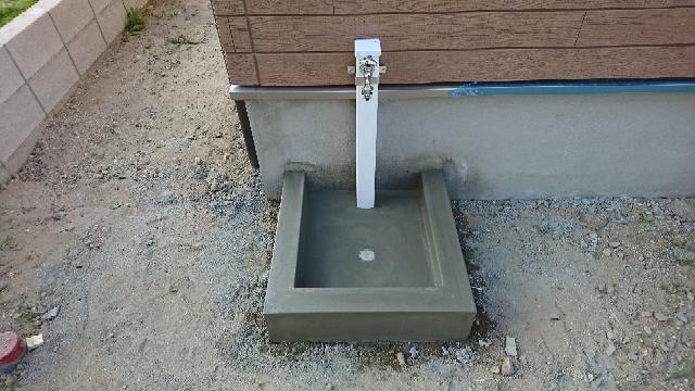庭の立水栓についてです。 ごく普通のを付けて貰いましたが、後から見直すと味気も無くもっとオシャレな感じにして貰えば良かったと・・・ 立水栓を交換するなら水受けのコンクリートを一部壊してからでないとむりですよね。 交換が無理なら、せめて見た目だけでも良く出来ないでしょうか。 シールみたいなのを貼るとか、外側をカバーするグッズとかご存知の方又は施工した方がいらしゃいましたらご教授願います。 水受けのコンクリート部分も何か良い案がありましたらお願いします。 コンクリート部分だけでも自分でタイル貼りにチャレンジしようかとも考えています。 写真は新築時の物で、外構は防犯砂利を敷いています。