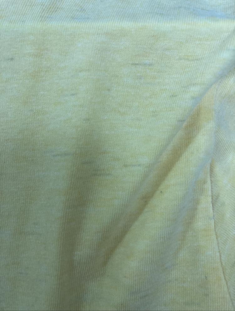 洗濯後のTシャツの汚れ?について 洗濯後に写真のような状態になっておりました。 見にくいと思いますが無地の黄色いTシャツに全体に黒い線状の汚れのようなものが襟元や袖の端までびっしりついており気持ち悪いです…。 なにが原因でしょうか? 他の洗濯物にはついていません。