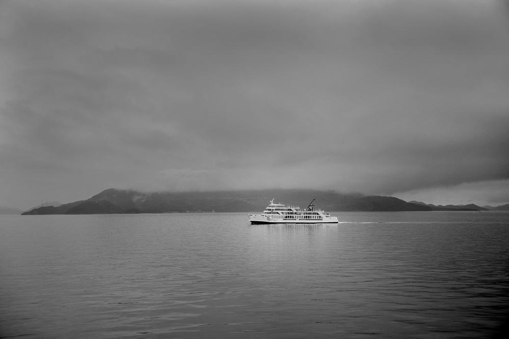 梅雨の重くのしかかる灰色の空で薄暗い瀬戸内航路。 また訪れるのは何年先になるかとデッキで港に向かう船を撮影。 日常繰り返される事と己の想いで特別に感じるギャップを貴方はどの様に考え写真に記録しますか。