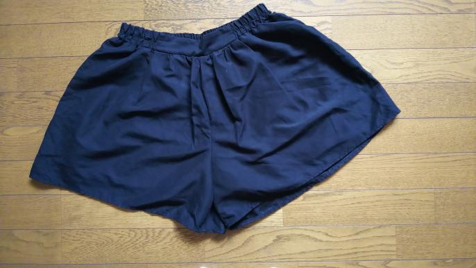 こちらのショートパンツに似合うトップスを教えてください。色は真っ黒で、私が着ると大きめです。