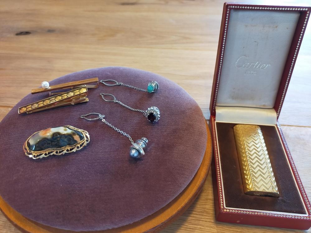 詳しい方よろしくお願い致します。 こちらのネクタイピンやブローチ、カルティエのライター(火花はでる)の価値を教えて下さい。 ネクタイピンは真珠かなと ブローチは瑪瑙かなと あとシルバーの3点は何に使うか分からないのですが、、、手前から 黒真珠 ガーネット×トパーズ?ダイヤ? グリーンは全く分かりません。 ライターは箱付きですが箱に昭和52年と手書きの記載があります。 全て本物だと思うのですが、詳しく知りたいときはどういった所へ持っていくのが正解なのかも知りたいです。 無知なものでお恥ずかしいですがどうぞよろしくお願い致します。