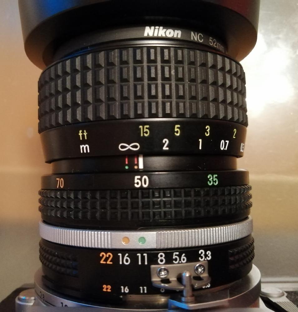 AI Zoom Nikkor 35~70mm を入手したのですが、絞りリングの上にある、オレンジと緑の点の使い分けがわかりません。 レンズを付けるとき(ガチャガチャするとき)は緑に5.6をあわせて使ってますがこれでよいのでしょうか。