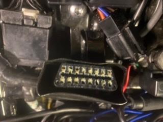 この写真の中心の端子?は何の差込でしょうか? バイクのシート下のetcカードを取り出そうとしたのですが、その時に取れてしまったかもしれません。近くに差し込めそうな所は見当がつきませんでした。 車種はトライアンフボンネビルt100です。 皆さまお知恵をお貸しください。