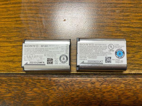 ZV-1のバッテリーについて質問です。 これはどちらが本物ですか? 調べると純正品と互換性みたいなのがあるとの事だったんですがハッキリとどれが本物!というふうには書かれてなかったのでお聞きしたいです、 青色の方は元々付属、青色でない方はSONYの方で予備バッテリーとして購入しました。
