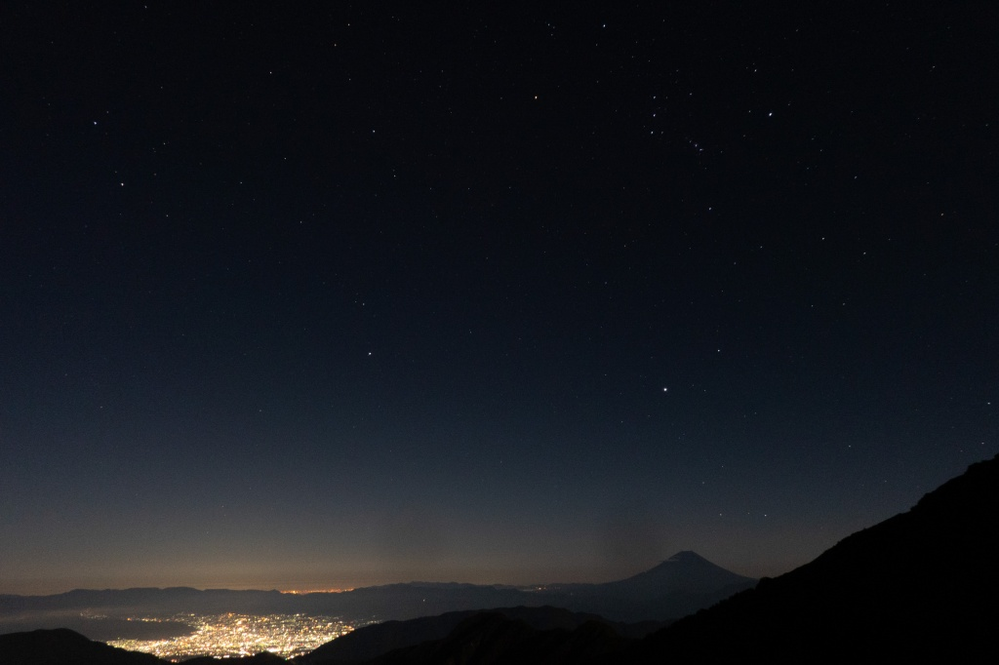 星景について。 甲府市の夜景と富士山と上空にオリオン座。 F値4、15秒、ソニーコンデジで撮りました。後ろからはかなり明るい月があります。 星が非常に暗いです。ただ、これ以上露出すると今度は町の明かりが強くなりすぎてしまいます。 こんなとき、どうやって、星も町もうまく撮ればいいでしょうか。
