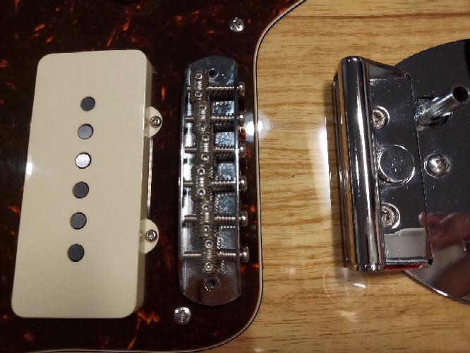 ギターのオクターブチューニングについて質問です。 先日ジャズマスターを購入したのですが、テンションが足りずバズストップバーを取り付けました。すると写真のようにドライバーを入れるスペースがなくなり、オクターブチューニング用のネジを回すことができなくなってしまいました。 これはバズストップバーを取り付けた弊害として受け入れるしかないのでしょうか。 それとも、L字型のドライバーのようなものがあり、それでオクターブチューニングをするのでしょうか。 初心者質問で申し訳ありませんが、どうか有識者の方、回答よろしくおねがいします。